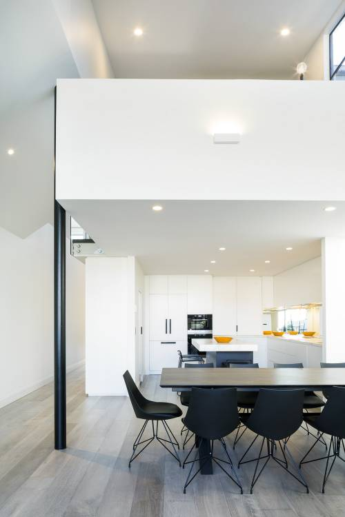Residential photography of modern kitchen and mezzanine with black chairs and table