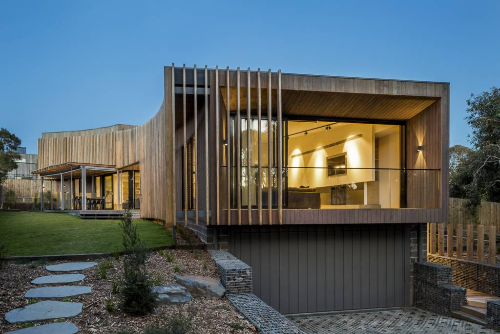 modern beach house photographed at dusk with large open window and wooden features