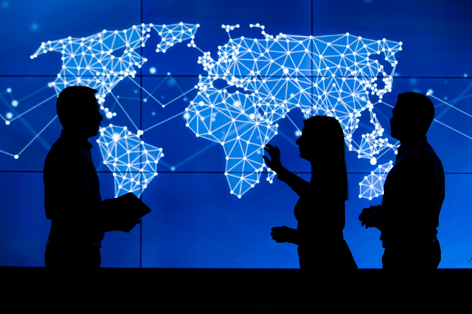 3 people silouette against screen with graphic world map in blue