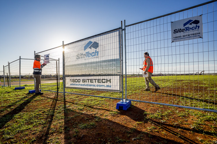 Sitetech workers fixing signs to construction fencing at dawn on residential estate for commercial photography branding