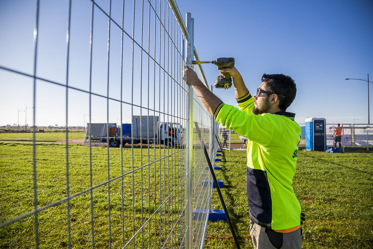 sitetech worker in high vis drilling the fencing with portable toilet and truck in background for commercial photography