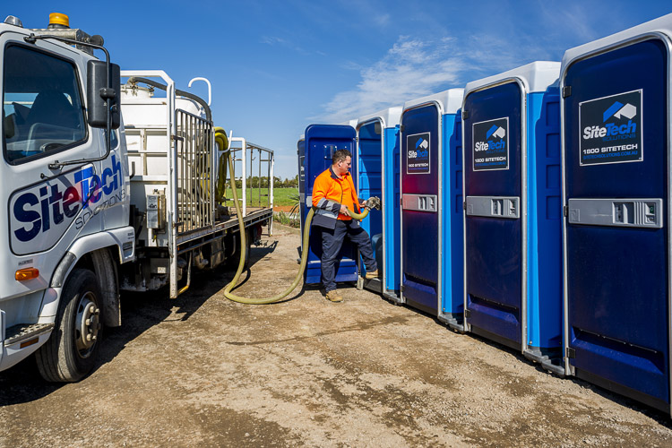 Sitetech truck parked with portable toilets in a row being cleaned by employee for commercial photography
