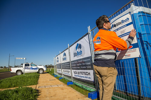 Sitetech employee placing oh&s sign on fence with ute in the background for commercial photography branding
