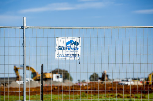 Sitetech fencing with sign and construction in the background for commercial photography branding