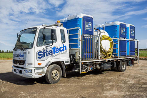 Sitetech truck with portable toilets parked on gravel with blue sky for commercial photography branding
