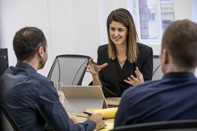 woman in boardroom meeting with two men gesturing with hands posing for workplace photoshoot