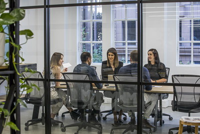 five people in boardroom meeting photographed through glass windows for lifestyle photoshoot