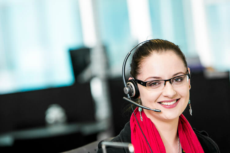 woman with glasses and red scarf with headset at call centre posing for corporate photography