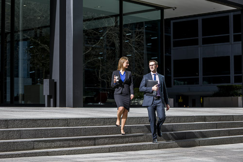 male and female lawyers walking down steps talking posing for branding photography