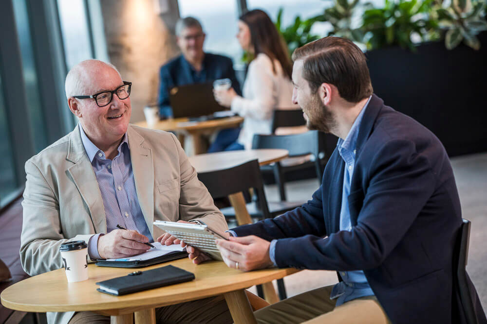 two men having a meeting in corporate breakout space posing for lifestyle workplace photography