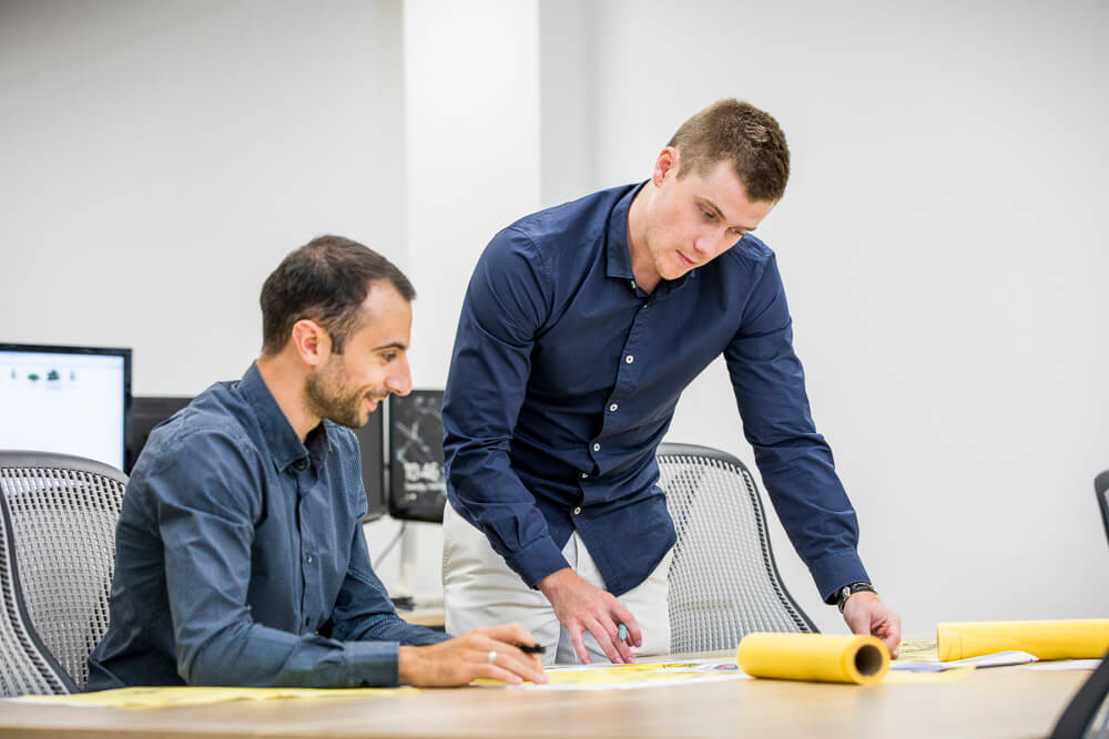 two men working over desk with yellow architecture paper for lifestyle photography photoshoot