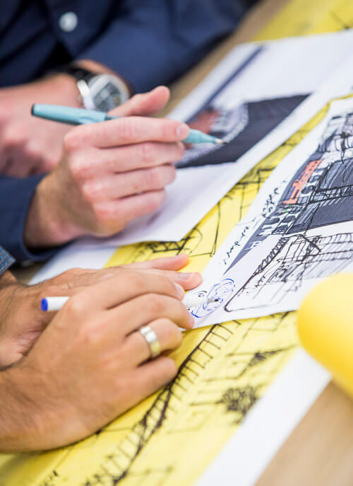 two hands with pens making notes over drawings and plans with yellow architecture paper
