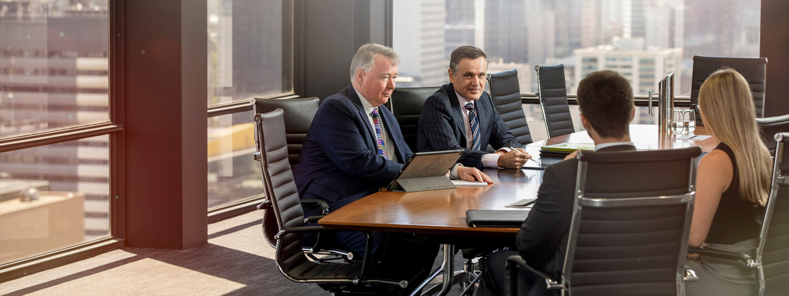 two male lawyers in boardroom with city views with clients posing for boardroom photography