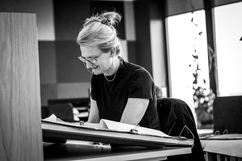 black and white image of older blonde female architect working at draft table