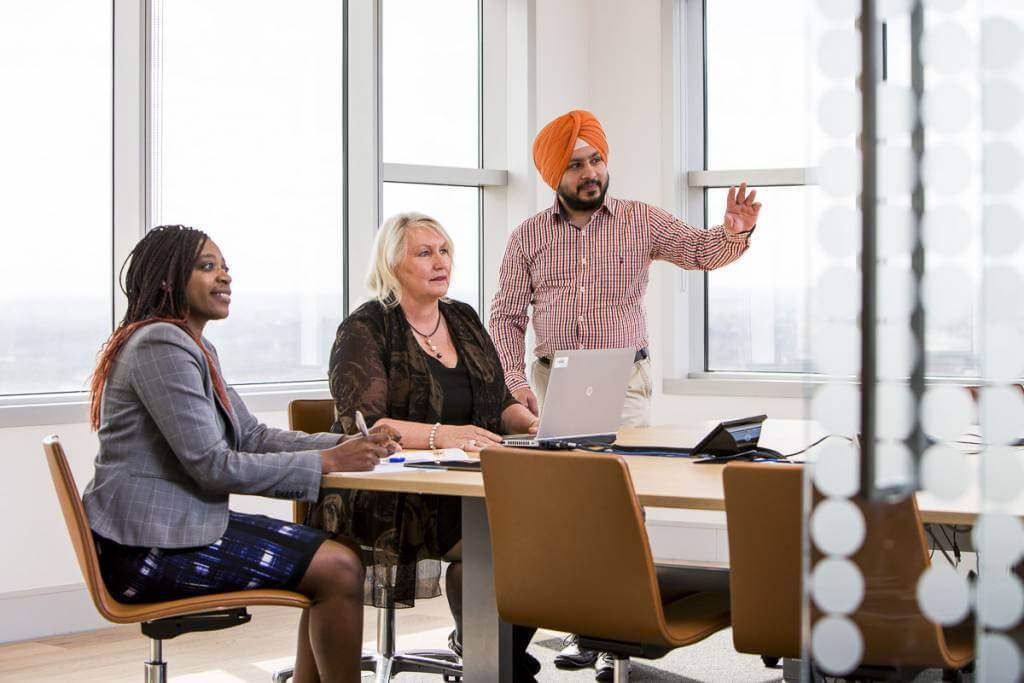 sikh man with older woman and african woman in boardroom looking at presentation posing for boardroom photography
