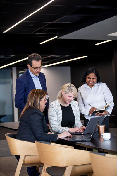four people consulting in breakout space with computer and notebook for workplace photography