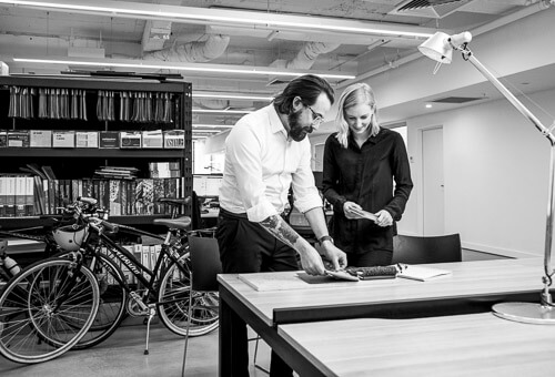 black and white photo of bearded man with tattoo and blonde woman at desk with bicycle in background
