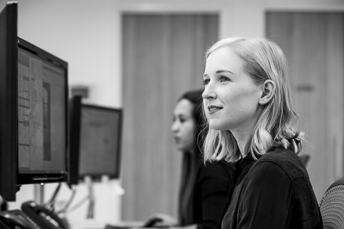 Close up portrait of young blonde woman at desk with computer screens for workplace photography