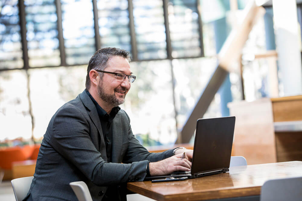 bearded man with glasses working at table with laptop in open office space