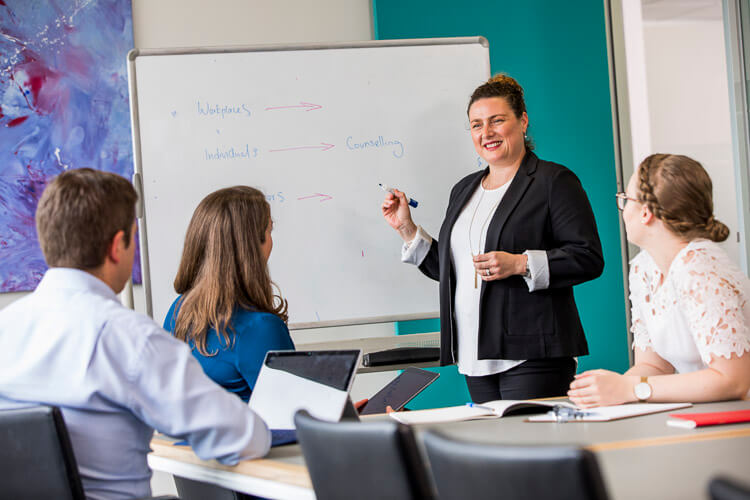 four people in boardroom setting listening to woman writing on whiteboard posing for workplace photography