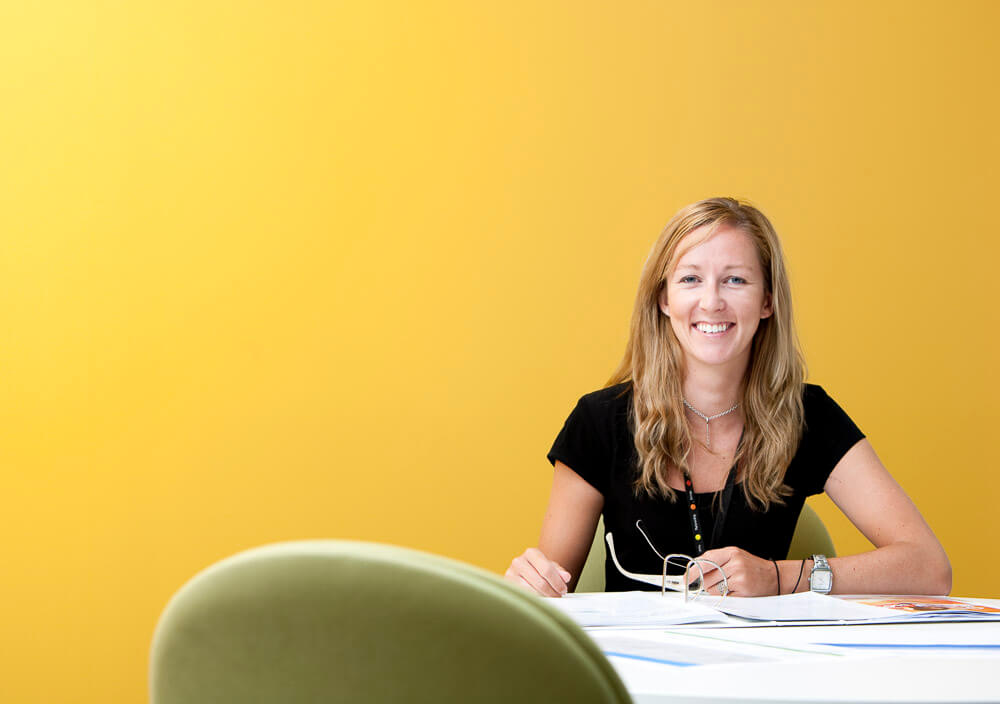 blonde woman in yellow meeting room with glasses in hand for workplace photography